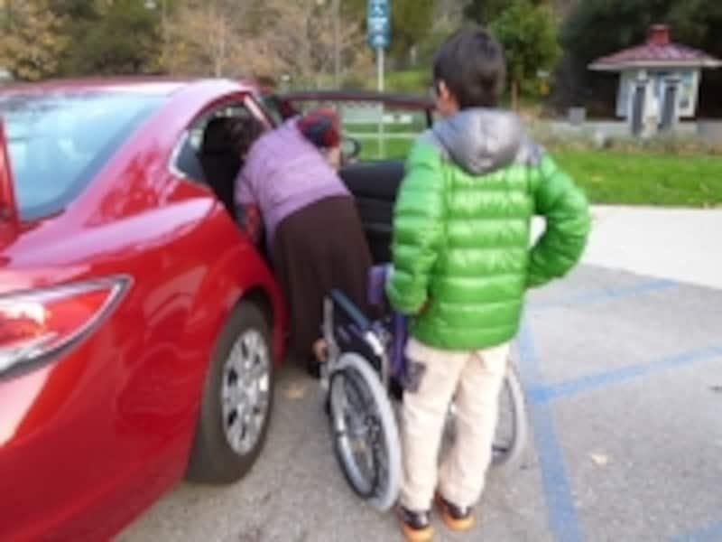 セダンの横に車椅子から降りた高齢者がセダンに乗り込もうとしている