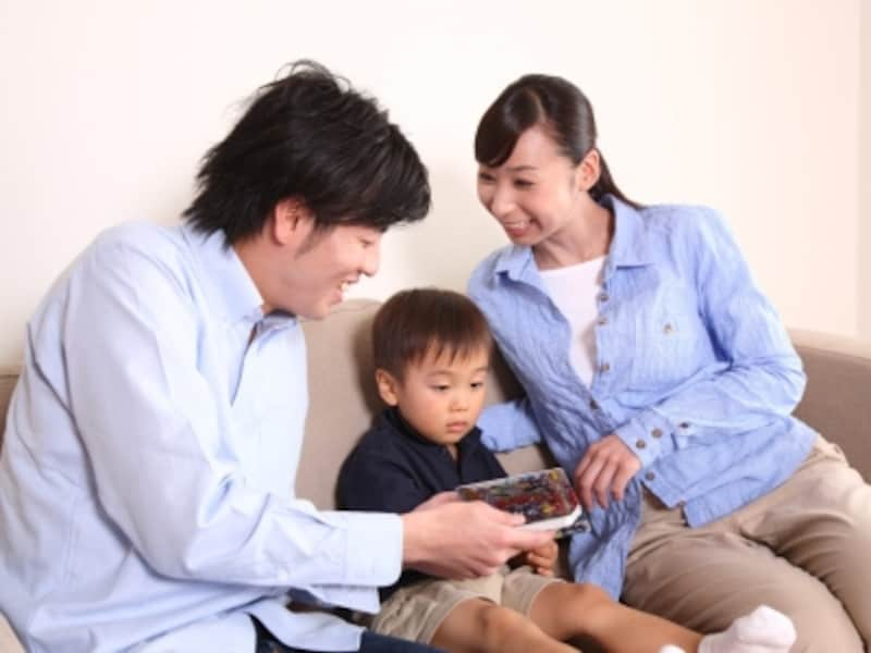 楽しそうに読み聞かせをする家族の写真