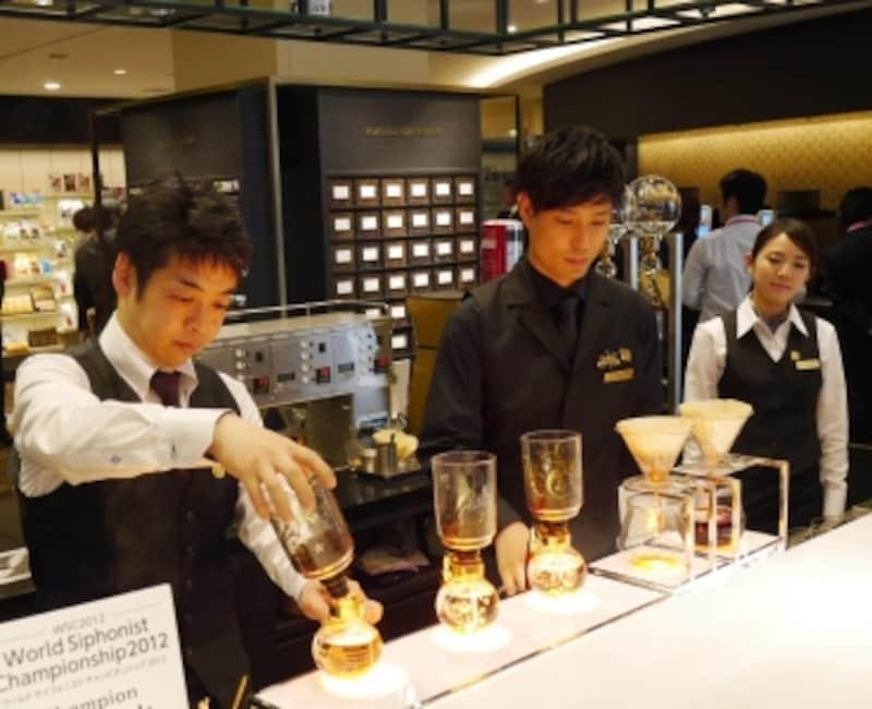 サイフォンとペーパーを使ってコーヒーを淹れるスタッフ