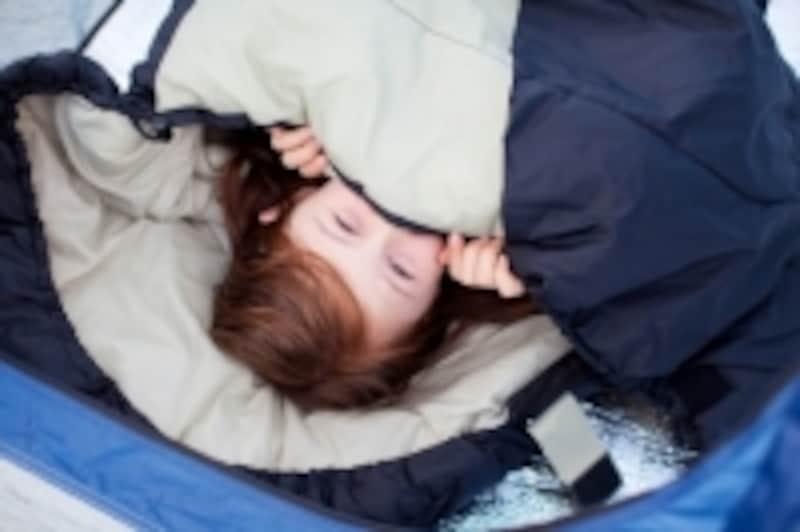 寝袋で眠る子供