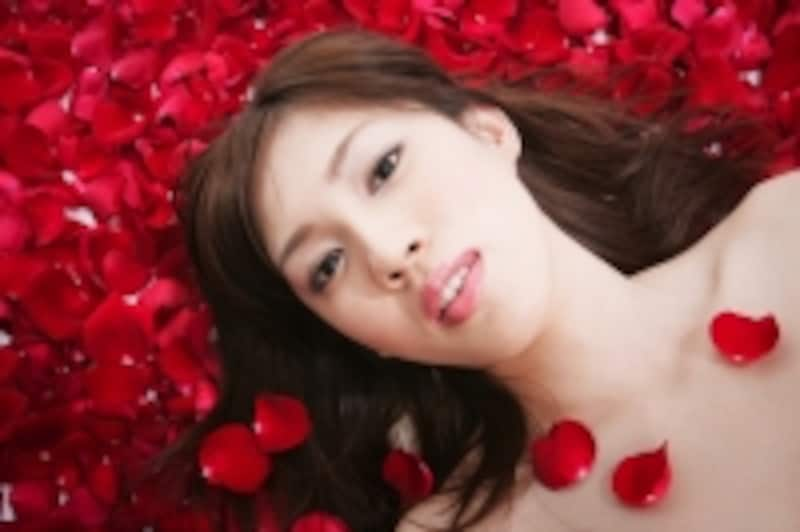 真っ赤な花びらの上に寝転ぶ女性