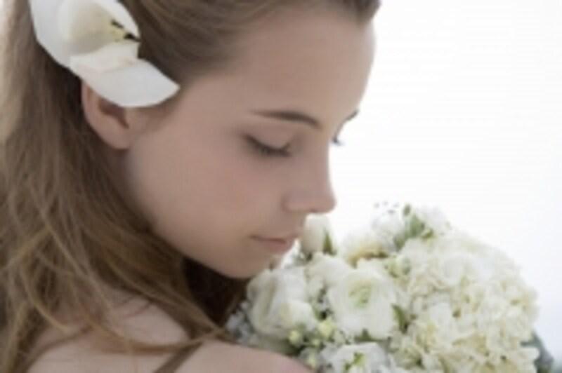 花をつけて下を向く女性