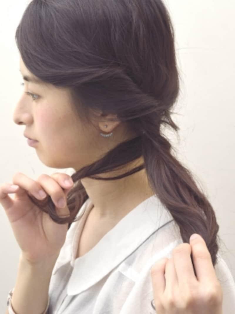 耳前の毛束をツイストしながら結び目に巻きつける
