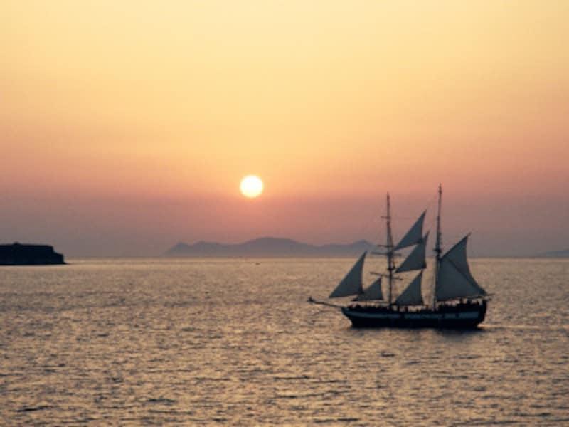 エーゲ海の夕日、水面を進む帆船とともに。こんな景色も船の旅ならでは