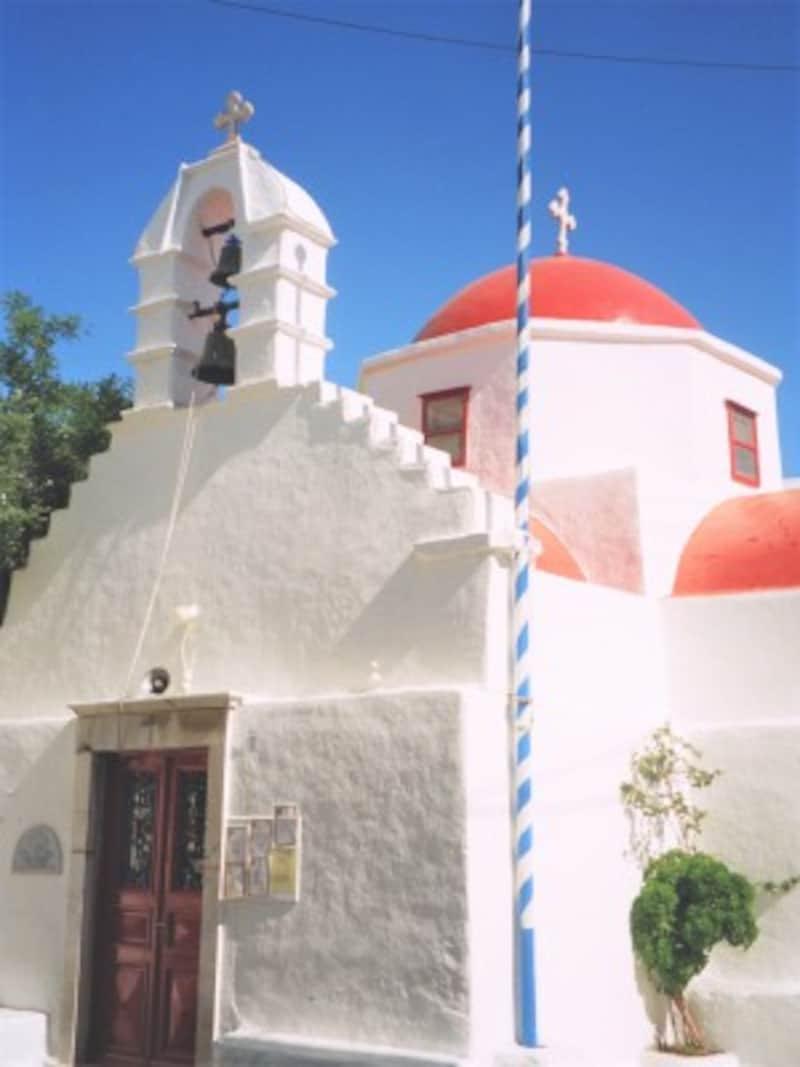 ミコノス島の教会。白壁の街並みが空の青や太陽の赤をいっそう引き立てる