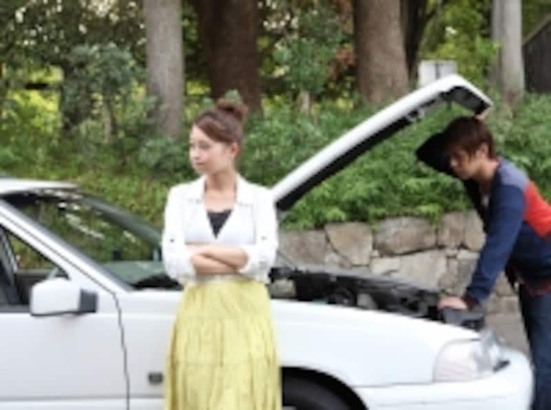 バッテリーが上がってしまった車を点検するデート中のカップル