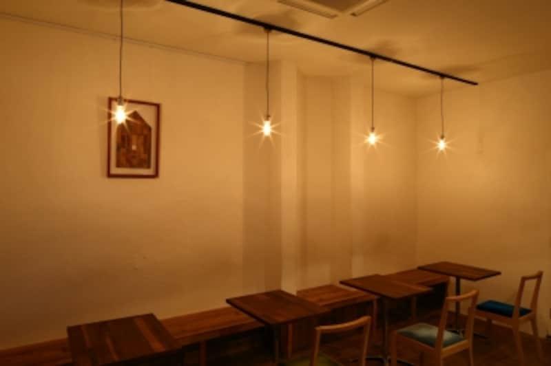 白い漆喰の壁に、全方向拡散型の照明が空間を照らします。各テーブルの上に照明器具が配置されていますが、テーブル上だけでなく空間全体に光が拡散されています