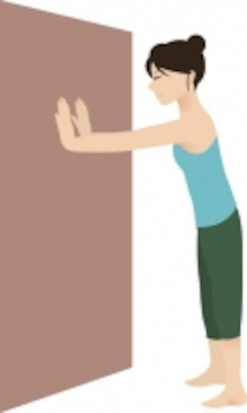 壁に両手をつく