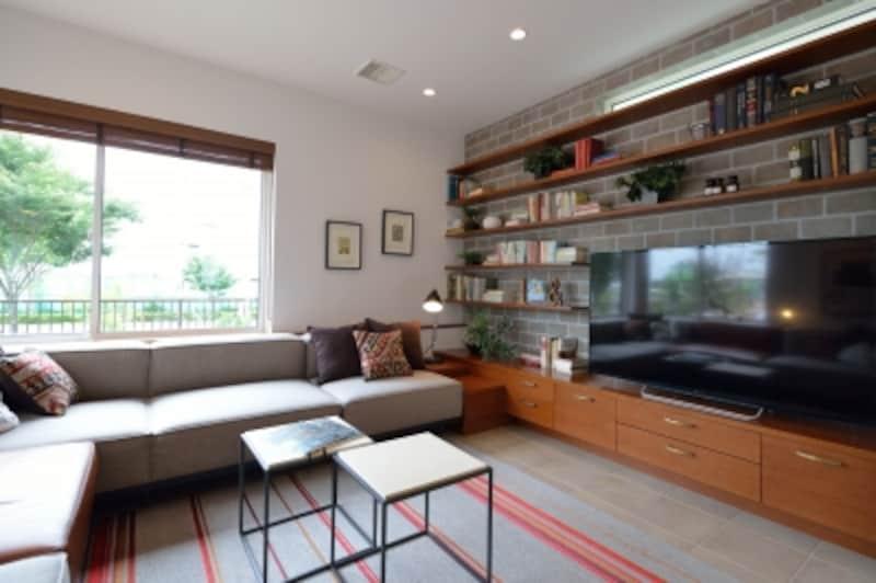 おこもり感のあるピットリビング。テレビ背面の床は、素材感あふれるレンガタイル張りで仕上げています
