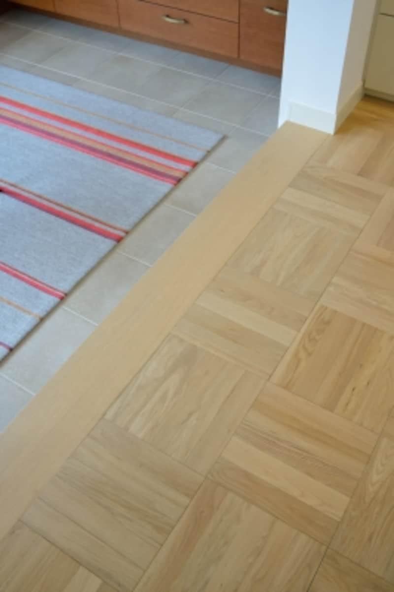 ピットリビングの床は正方形のタイル。キッチンの床をパーケットフローリングにすることで正方形のモチーフを揃え、デザインの連続性をさりげなく表現しています