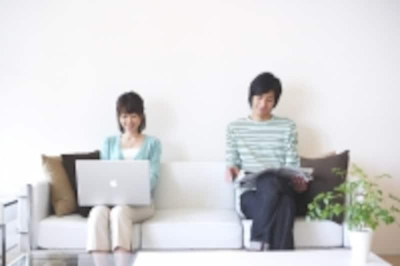 パソコンをしながら離れて座る男女