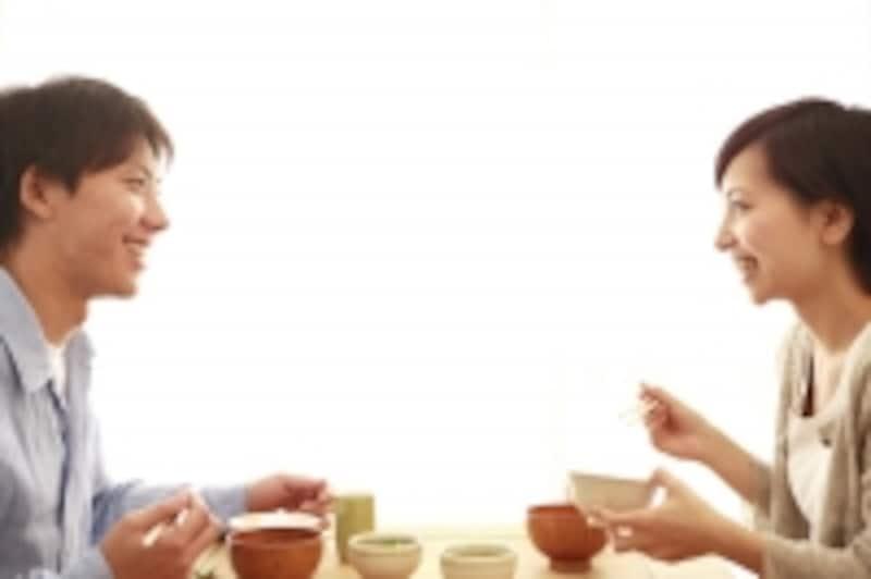 向き合って食事をしながら話している男女