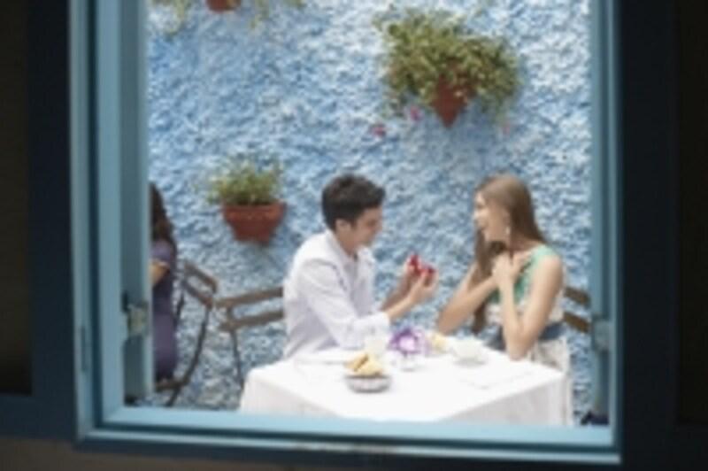 白い椅子とテーブルで食事をしている男女