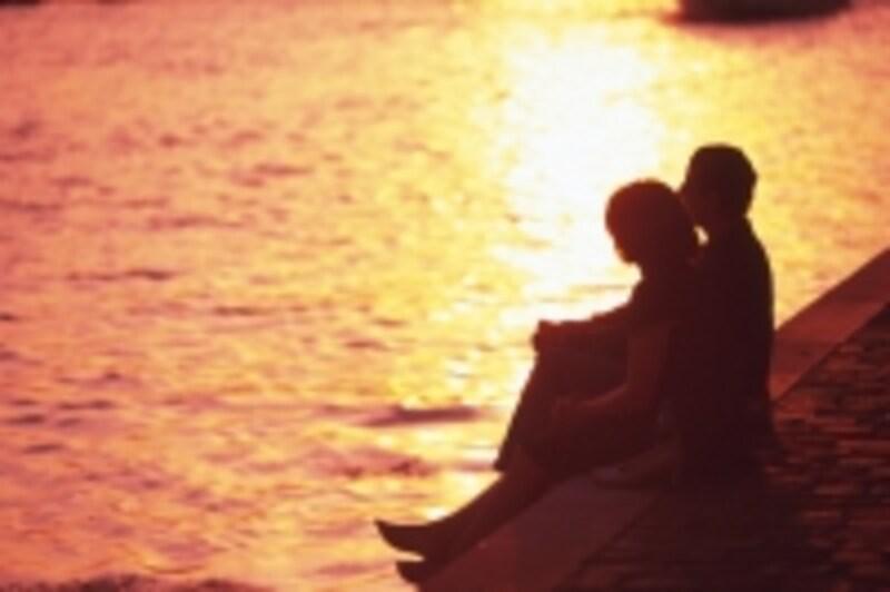 夕焼けに座る男女