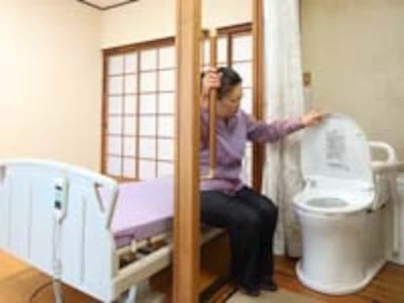 ベッドからベッドサイド水洗トイレへ、お母様が移動するときの様子を再現するIさん。介助に加え、柱に備えられた手すりの利用も欠かせません(手すり工事を除いた工事費用は15万円。なお費用は現場によって変わります)