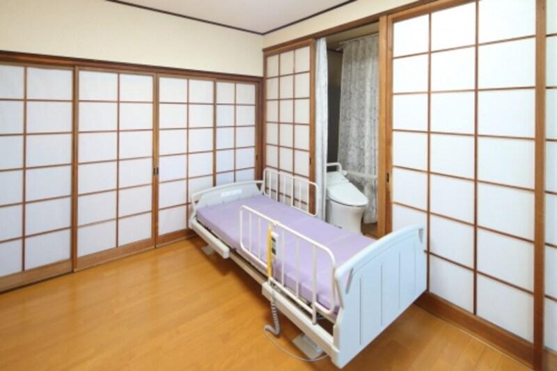 Iさん宅のベッドサイド水洗トイレはカーテンの仕切りを設け、お母様が利用するベッドの隣に設置