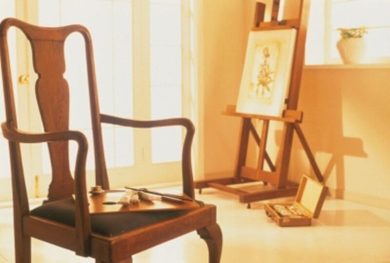 部屋の中にはいすとイーゼルに置かれた絵画