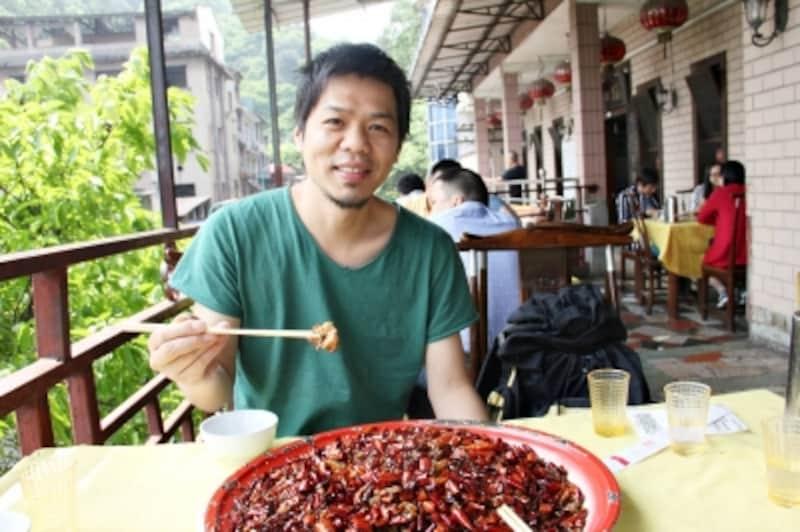 歌楽山辣子鶏を食べているガイド