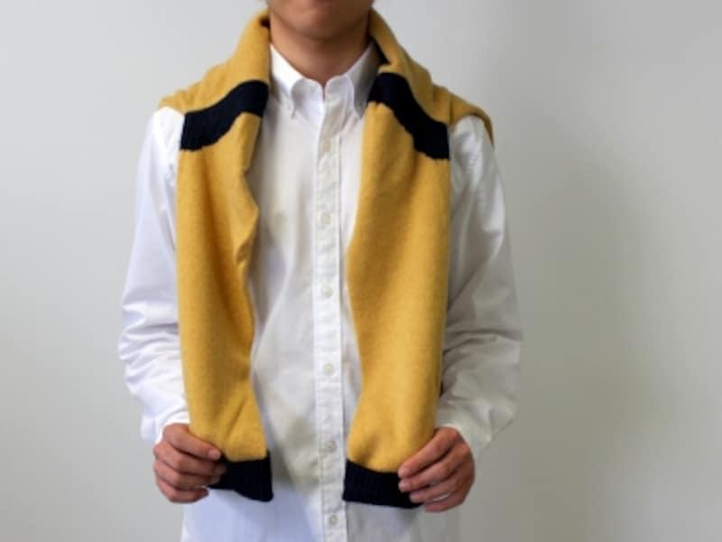 セーターを背中に羽織るようにして、肩から袖を垂らして