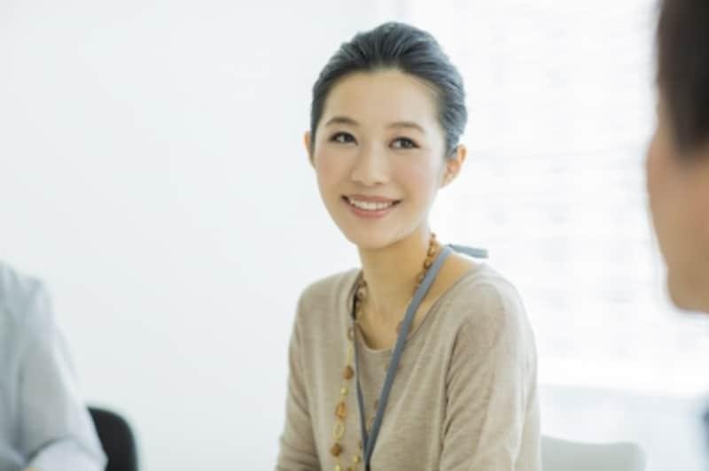 笑顔で会話をする髪をアップしている女性