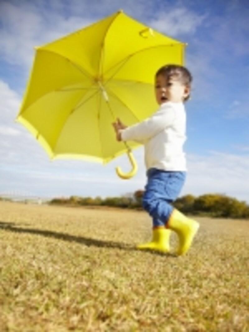 青空の中で傘をさす子供