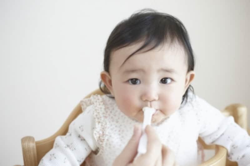 お母さんにスプーンで食べさせてもらう赤ちゃん