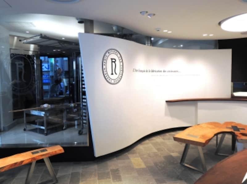 看板商品「エスカルゴ」をイメージした有機的な曲線を描く白い壁、ガラス越しに眺められる厨房はここ、青山の路面店にも