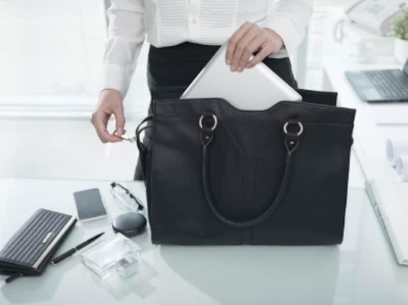 仕事用のバックからメイク道具や書類を取り出す女性