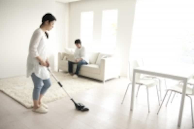 掃除をする妻、新聞を読む夫