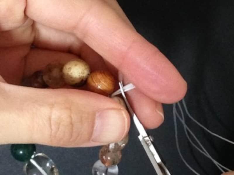 中央の茶色い木玉に結び目を入れます