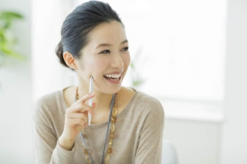笑顔で話しをしている髪を一つに束ねた女性