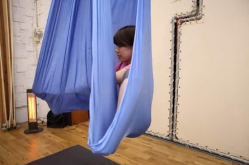 布をまたぎ、つま先まで布を伸ばして中に座るようなポーズをとります