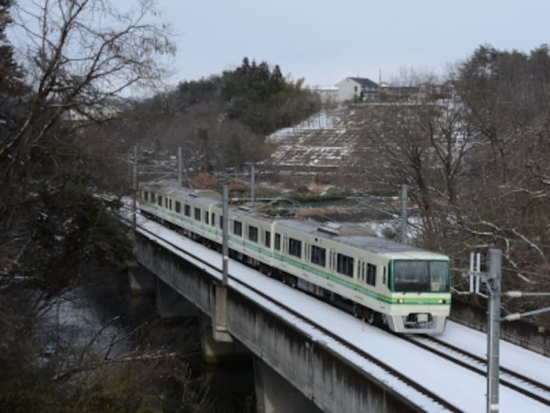 黒松駅付近のため池を渡る電車