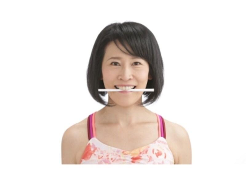 写真3:歯に割り箸をくわえたまま、笑顔をキープし、「キラリスマイル」。