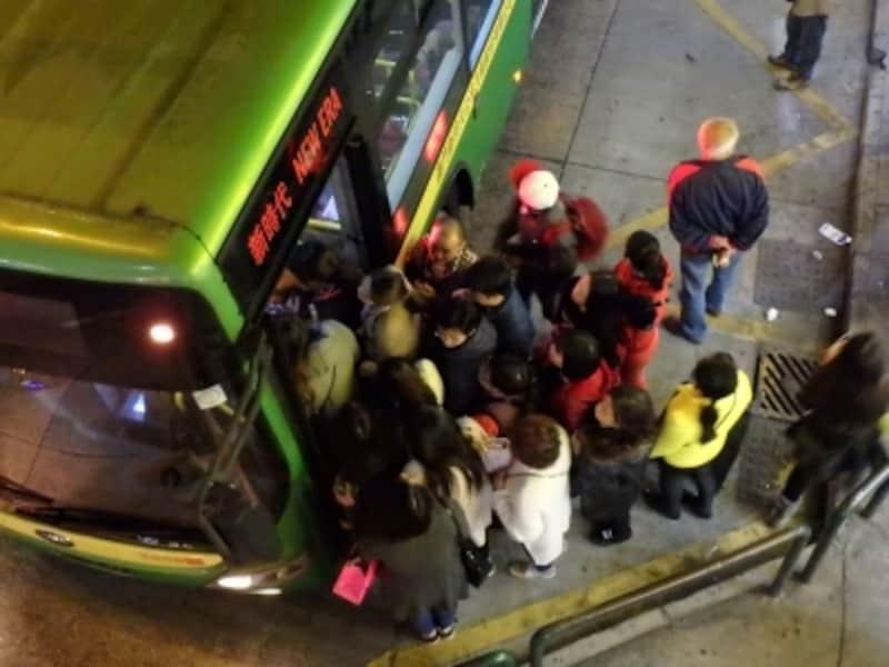 満員のバスに乗ろうとする人