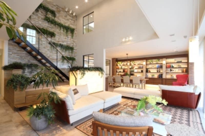 自由な方向に向いて座れるソファのレイアウトが新鮮!階段横の壁は、石を張りアクセントウォールに。インテリアグリーンが、石の素材感をより際立たせています