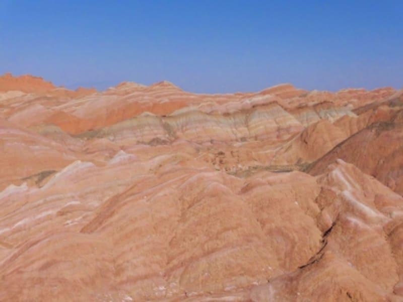 赤みがかった堆積層が幾重にも折り重なる