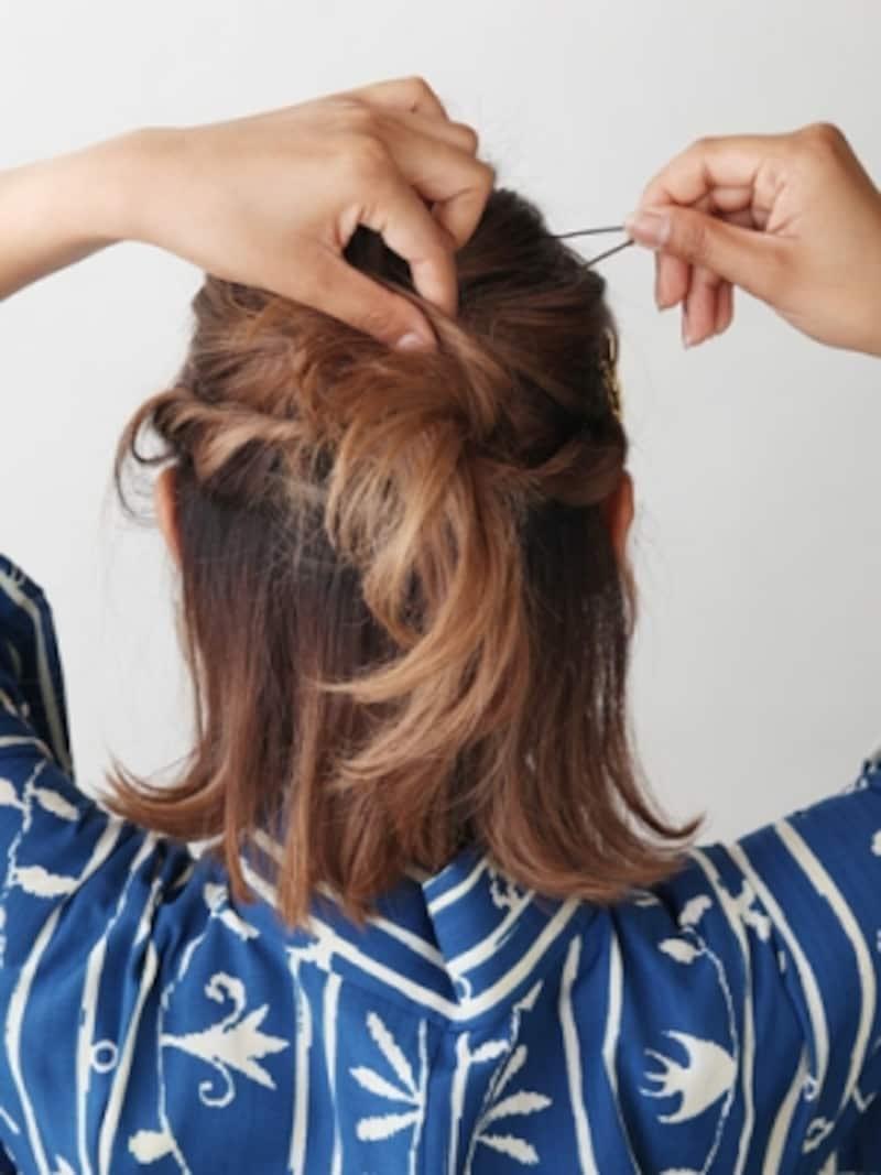 くるりんぱの結び目に毛束を巻きつける。