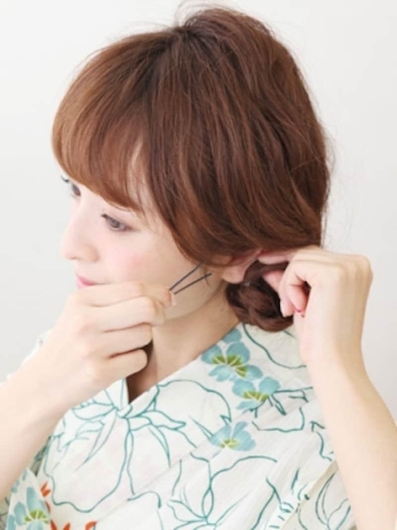 三つ編みを内側に折り曲げ、毛先を隠しながらピン留め