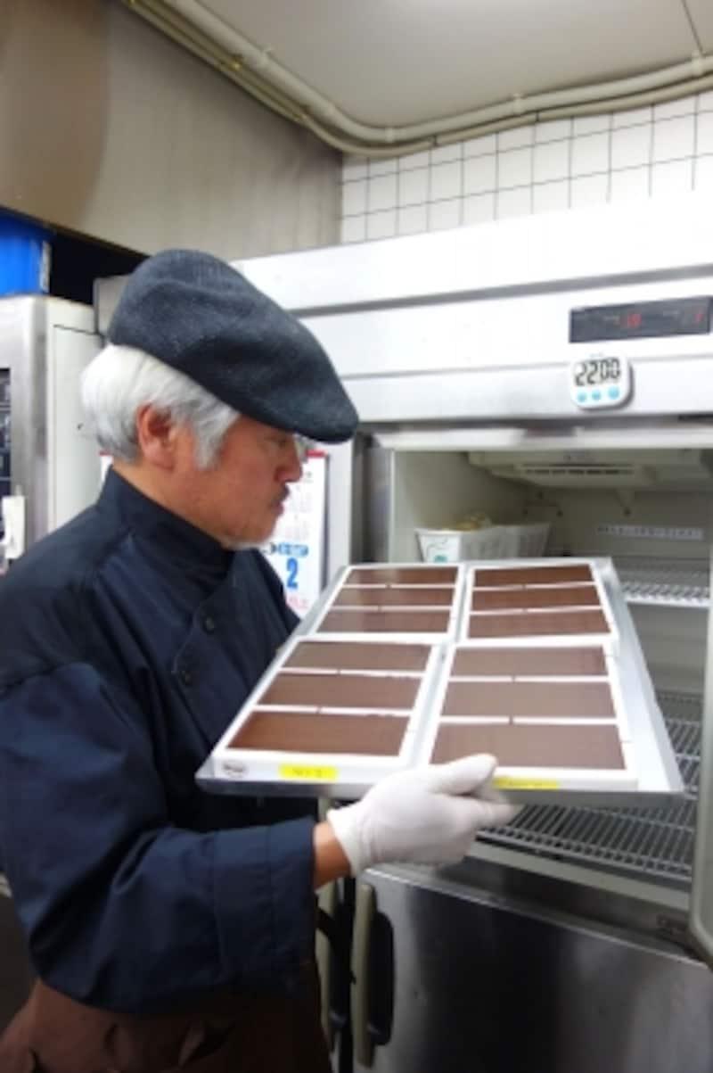 完成したばかりのチョコレートをチェックする三枝俊介シェフ
