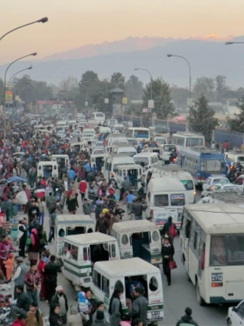ヒマラヤの山並みをバックに夕刻のカトマンズで客を集めるテンプーの群れ。大気汚染が進む今なお庶民や旅行者の重要な移動手段に変わりはない。