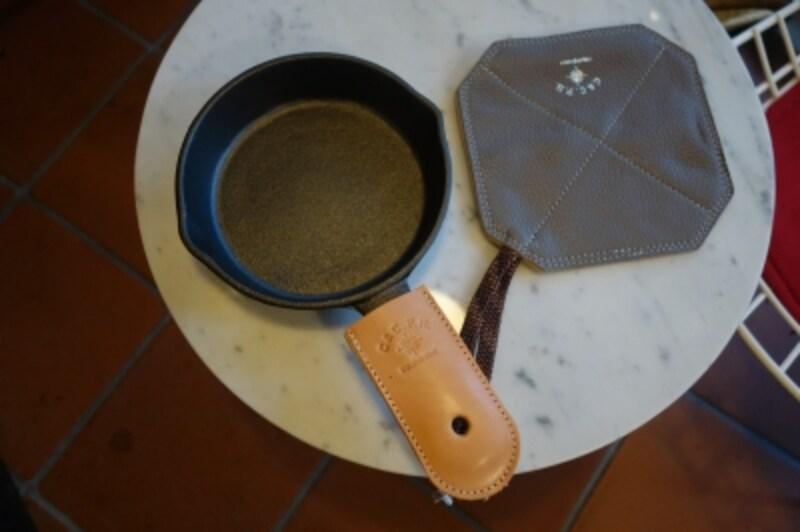 小ぶりのスキレットは人気アイテム。取っ手用レザーカバーとセットで。鍋つかみ兼鍋敷きもシンプルなデザインのものが揃っています。普段は自宅で使ってもOK。