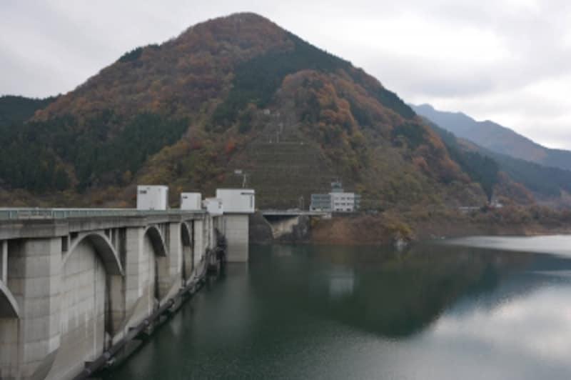 湖岸も湖面も紅葉の色彩で覆われる浦山ダム