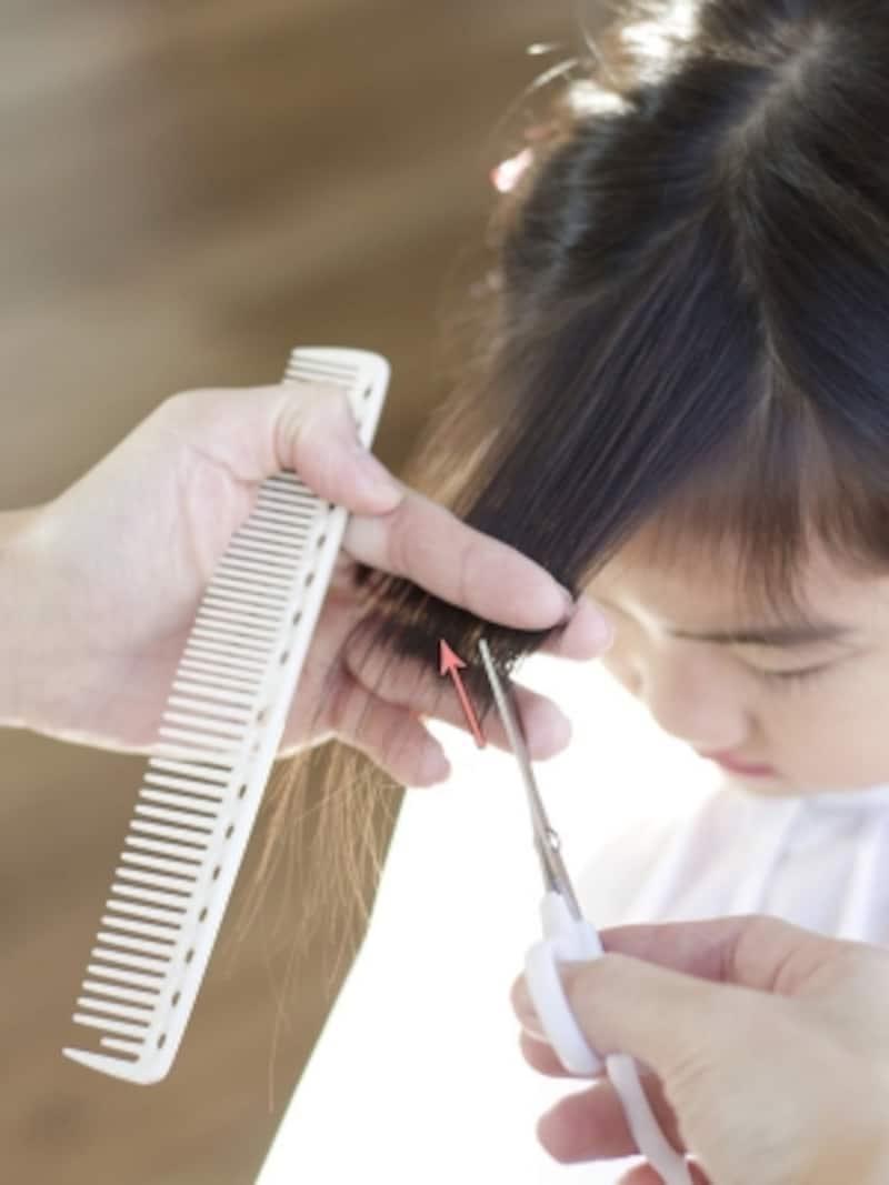 前髪を手前に引き出しながらカット