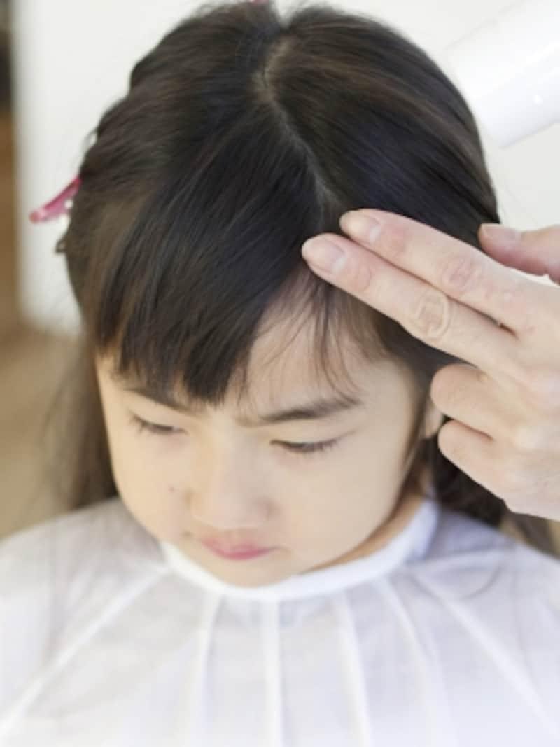 前髪にドライヤーを当てて余分な毛を落とす