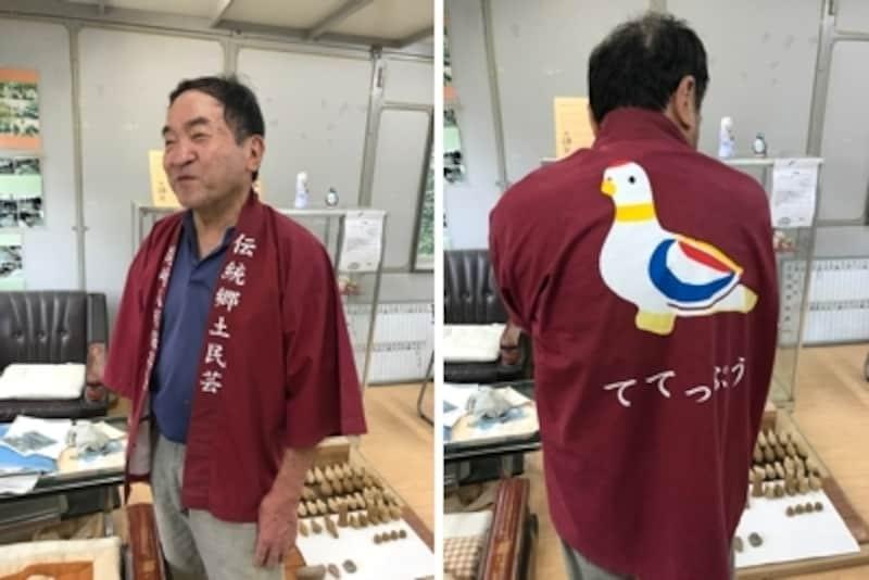 尾崎人形の作り手、高柳政廣さん。鳩笛の絵柄の法被を着てくれました。