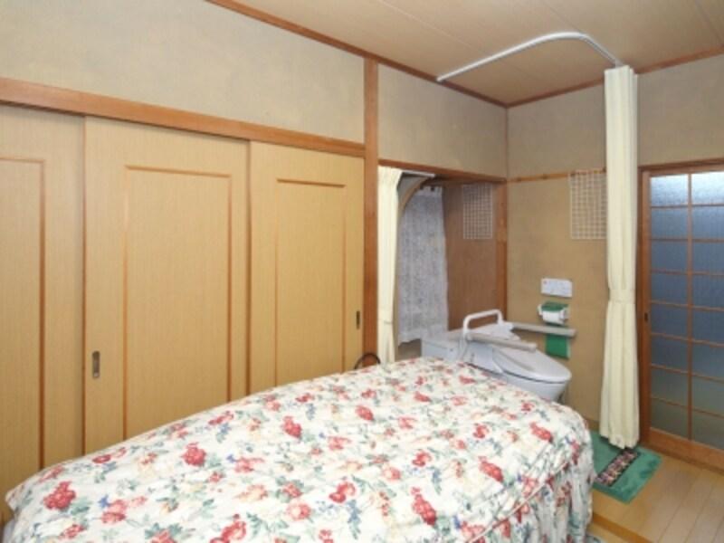 Sさんの寝室を掃き出し窓側から撮影した写真。奥の右手にあるのが茶の間への引き戸で、「ベッドサイド水洗トイレ」は左手に設置されています