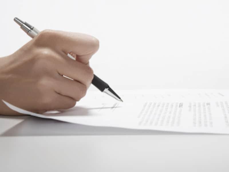 保証契約書にサインを交わす人
