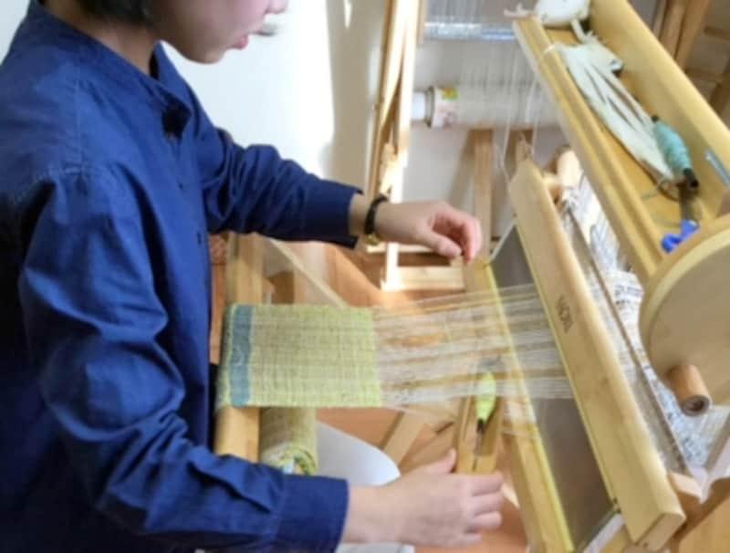 昔ながらの足踏み織り機で、マフラーを織っていきます