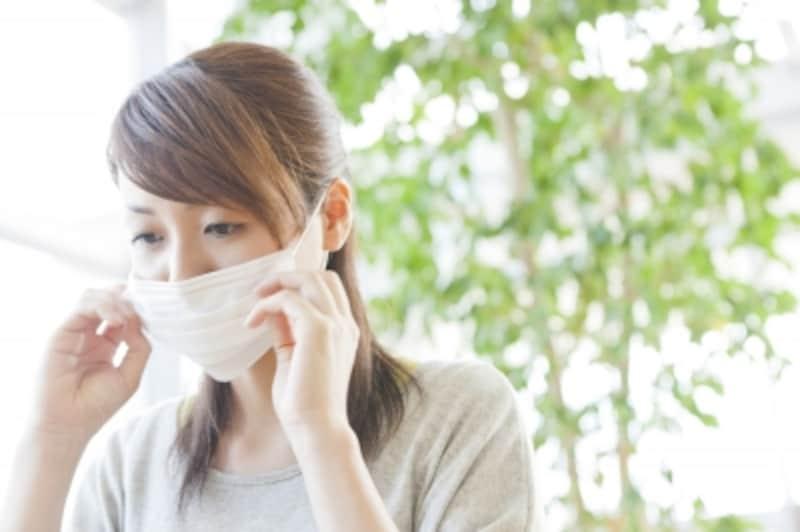 マスクをつけようとしている女性